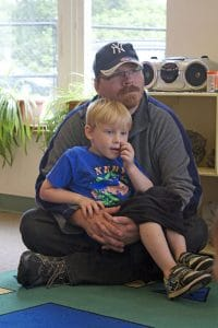 Dad and son listen together at Read With Me.